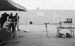 Modern ammunition testing. Paul Nowak of Winchester (left, with Springfield Armory pistol) fires over a chronograph (on tripod) which measures the bullet's velocity, and into the block of ballistic gelatin set on steel holder at right.