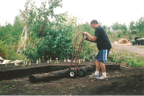 My son, David, helps build raised garden beds out of railroad ties.