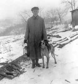 Major Belville with a foxhound and a lamp oil lantern on a cold winter evening, circa 1920. Belville was something of a Paul Bunyan character known for hard work. Armed with a sharp axe, he attacked the great oak trees on his land, turned them into lumber, left the ground in shape to farm. When it got dark, he lit the carbide lamp on a miner's cap, chopped on through the night.