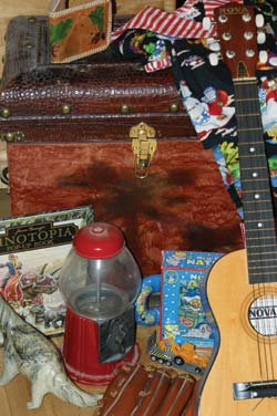 A pop-up book, toy dinosaur, child's beginner-sized guitar, baseball glove, and antique bubble gum machine...just a few treasures to cash in on from an old attic trunk.