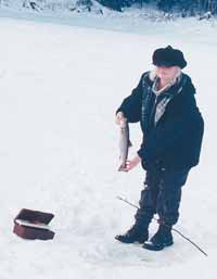The author caught this nice supper trout through the ice using just some line, a sinker, a hook, and a worm tied onto a willow stick.