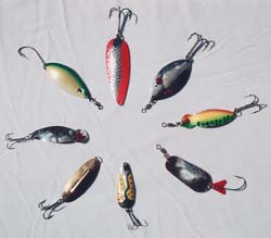 My pick of hard water lures that offer good action for jigging and lots of underwater flash—clockwise from the top: Red Gold Gibbs, Two Eye Lucky Strike, Gibbs One Eye Wiggler, Gibbs Kit-a-mat, Jumbo Kamlooper, Gold Williams Wabler, Silver One Eye Lucky Strike, Green-yellow Ruby Eye.