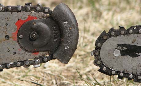 "Two types of anti-kickback devices. The Homelite saw on the left prevents kickback by shielding the end of the bar so that the chain can't contact the wood as you cut. The saw on the right uses a special link with a long ""tail"" between the cutting links to prevent kickback. The ""tail"" extends outward as the chain comes around the end of the bar and pushes the chain away from the wood so that the cutting links cannot make good contact."