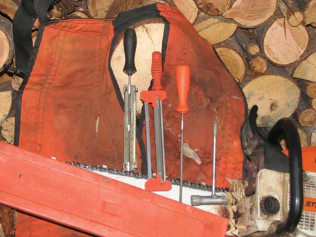 Chain sharpening accessories I take to the woods with me when cutting. Left to right: the file guide I use for my McCullough Mini-Mac, the file guide for the Stihl that files the depth gauges at the same time you file the cutting teeth, a file for the Stihl, and the combination tool that's used to adjust the chain tension and remove the spark plug.