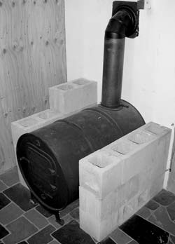 Assembled barrel stove on a concrete floor. Concrete blocks will have small stones dropped into cavities for extra bulk. The barrel rests against a concrete wall using it as part of its heat sink. The blocks and some air space protect the wood wall on the far side.
