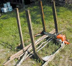 Rack for cutting branches and tree tops at the wood lot. The width between the uprights is about four inches shorter than the length of the bar of the chainsaw. The rack is shown here with just a few limbs. When filled you can cut hundreds of pieces of wood to stove lengths in minutes.