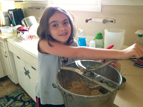 Managing Editor Annie Tuttles's daughter, Olga, helps to make bread for the family's evening meal.