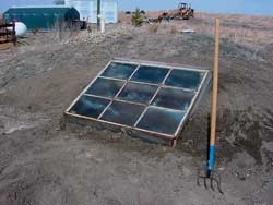 A window is placed over the top of the completed hotbed, and it is ready for growing seedlings.