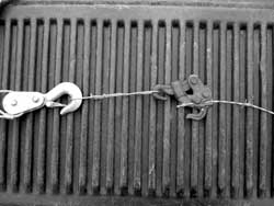 How a fence clamp is used. The business end of the come-along at left is attached to the clamp with a small loop of wire. The clamp is then attached to the end of the wire to be stretched.