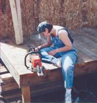 Juanita sharpens a chainsaw on the front porch of our cabin-in-progess.