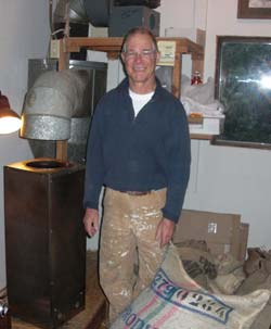 Jim Van Camp stands among sacks of raw coffee next to his Sivetz roaster in his home-based roasting room.