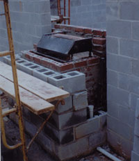 Rear view of hydronic woodstove being bricked into masonry fireplace