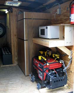 Interior view of completed trailer showing solar powered refrigerator, microwave oven, and backup generator. Not pictured are the waterless composting toilet and utility sink supplied from plastic water tank above.