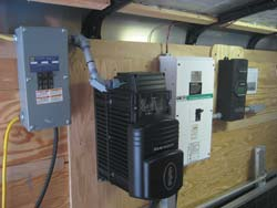 OutBack sinewave inverter with 120 VAC circuit breaker panel (left) and 24 volt DC disconnect panel on right. Solar charge controller is located at extreme right.