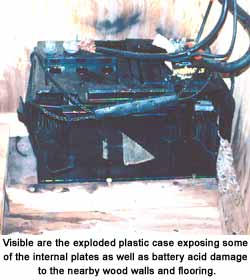 Visible are the exploded plastic case exposing some of the internal plates as well as battery acid damage to the nearby wood walls and flooring.