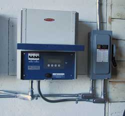 Photo 1: One of two Fronius 3-kW grid-tie inverters. Note the DC-rated safety disconnect and all high voltage wiring installed in metal conduit.