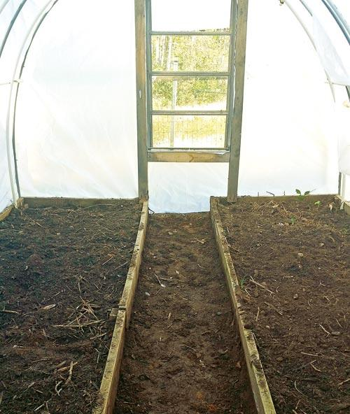 The inside of the greenhouse has a two-foot-wide walkway through the middle. There are windows on each end to make it easy to ventilate.