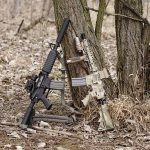 Two AR-15 rifles standing on a tree
