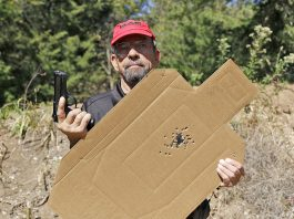 Massad Ayoob holding his Wilson Combat Beterra 92 and the target that he shot with it.